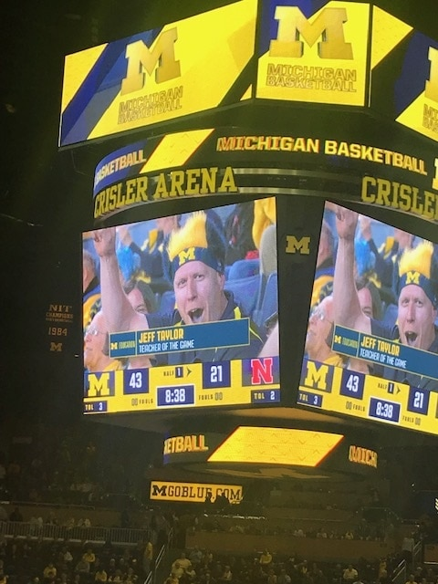 "Jeff Taylor, '00, was spotlighted as ""Teacher of the Game"" at the last Wolverine basketball home of the 2018-19 season—a game that turned out to be head coach John Beilein's last game at Crisler Center. Jeff is in his 20th year teaching, all in the Ann Arbor Public School, and has coached over 75 youth sport teams. He is a middle school science teacher at Clague Middle School."