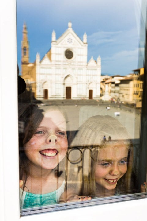 two girls enjoying the view at their window over Piazza Santa Croce in Florence