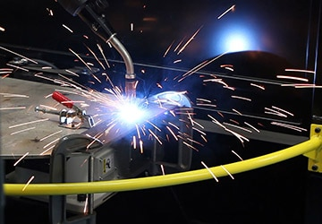 Image of a robotic welding MIG gun with sparks