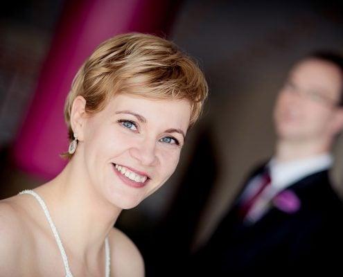 schickes Portrait der Braut mit Bräutigam unscharf im Hintergrund