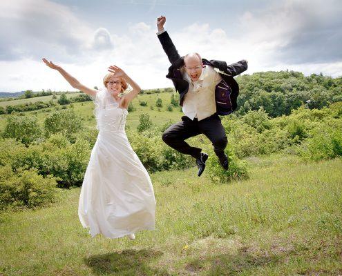 Hochzeitspaar springt zusammen hoch
