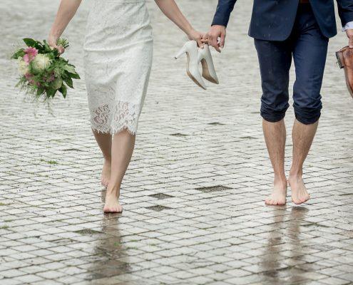 Hochzeitspaar barfuß im Regen