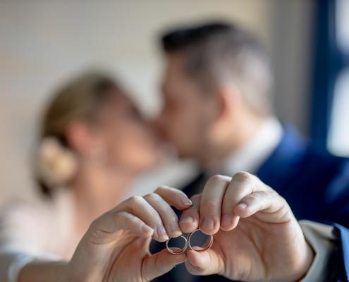 küssendes Brautpaar hält die Ringe in die Kamera