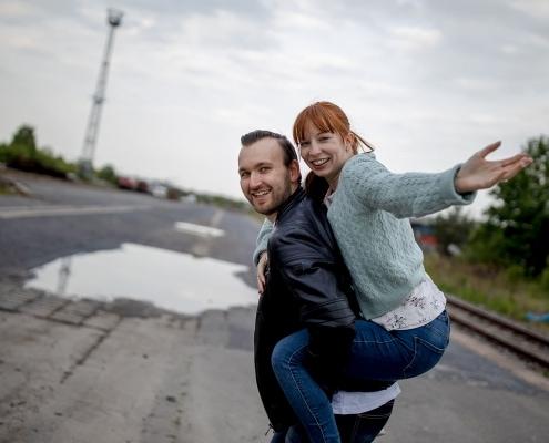 Huckepack in einer Drehbewegung fotografiert, beide lachen in die Kamera Canon EOSR & EF 35mm f/1.4l ii usm