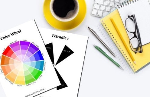 Colr wheel template and color scheme guide on desk with keyboard, coffee, pens, and notebook