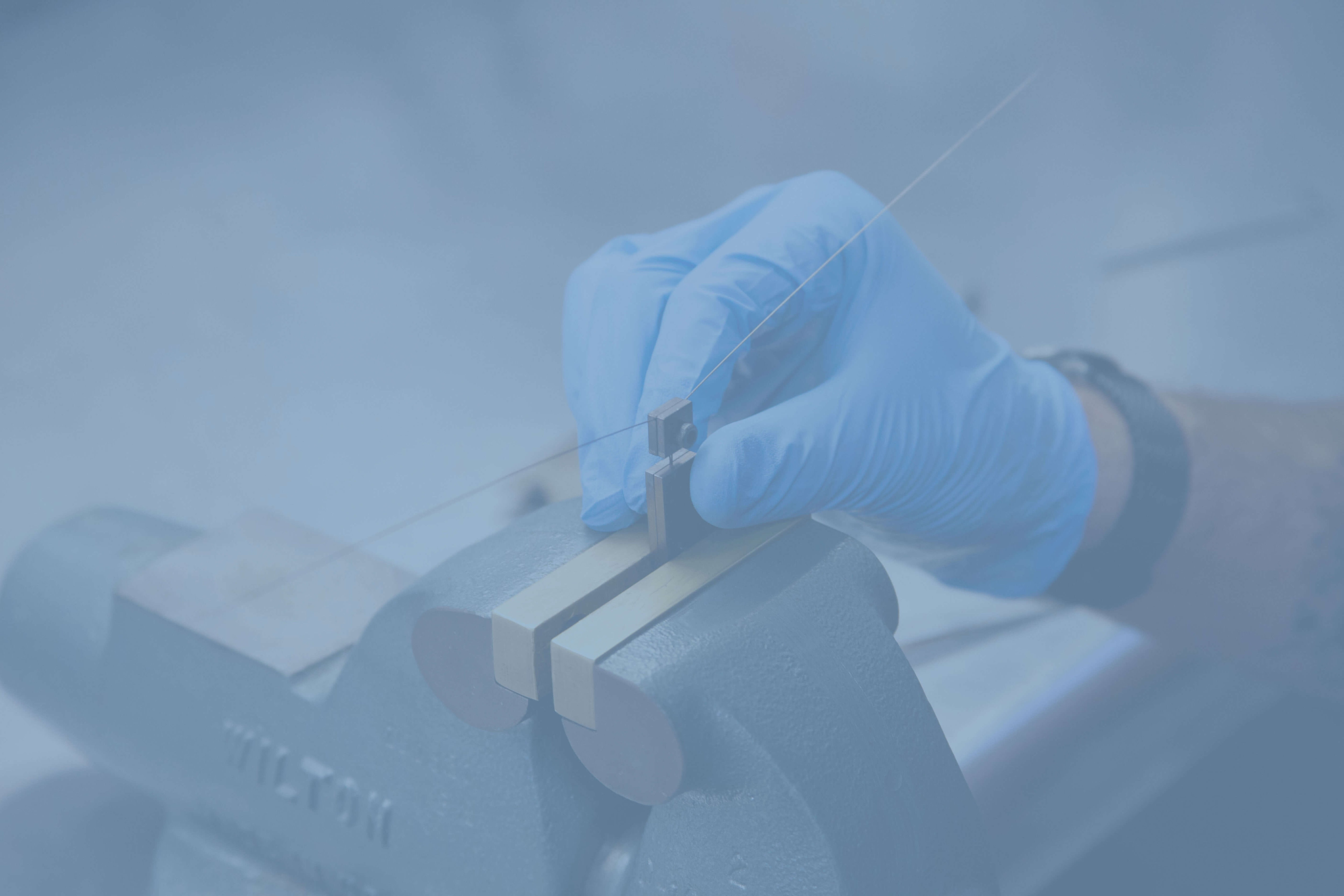 hand with a blue glove working on a medical device with a blue overlay