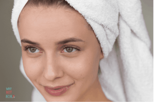 young woman with clean beautiful freshly washed skin with towel wrapped on her head
