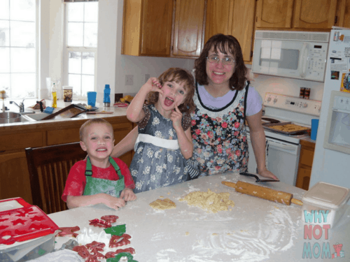 mom with son and daughter making decorated sugar cookies with flour on their faces
