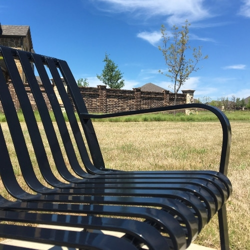 metal bench in grass in front of brick home