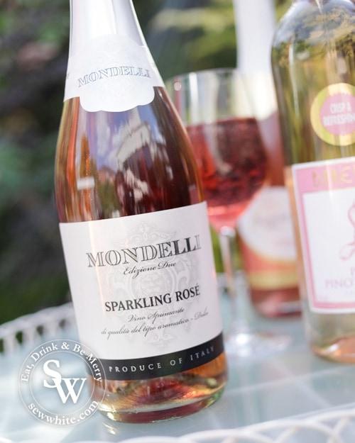 Mondelli sparkling Rose bottle on a garden table