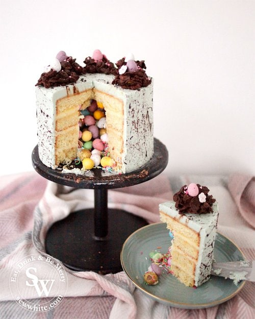A beautiful Speckled Easter Pinata Cake with tumbling mini eggs and a slice ready to serve