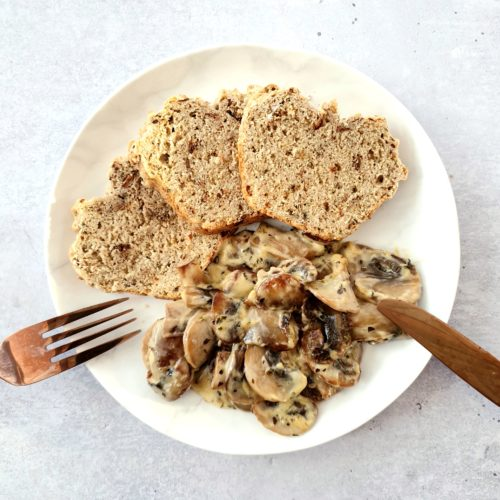 Close cropped overhead shot of mushrooms on a white plate with 3 slices of soda bread. Knife and form rest on the plate sides as though eating has started.