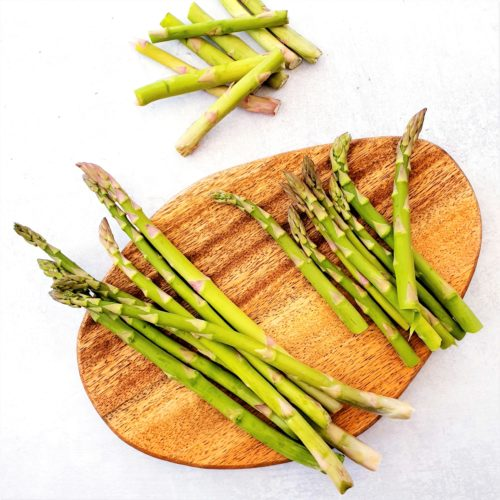 Asparagus show on a wooden board. Some are whole and others are prepared by snapping. The discarded sections are show to the side.