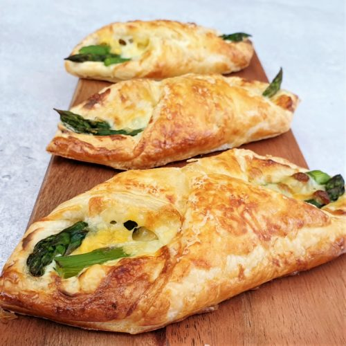 3 puff pastry asparagus wraps shown on a thin wooden board at a shallow angle.