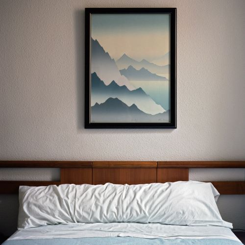 Bed with gradated mountain artwork above