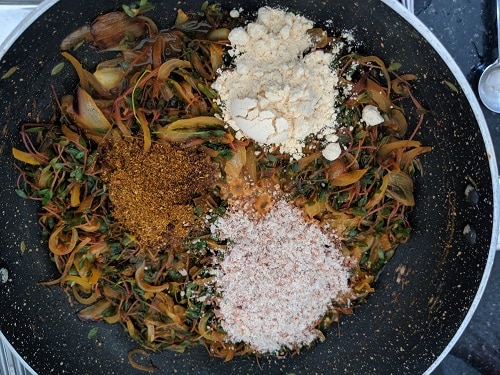 Adding spices and goda masala to chival bhaji