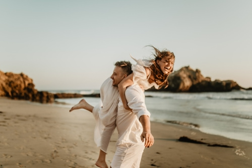 young couple dressed in white eloping on the beach