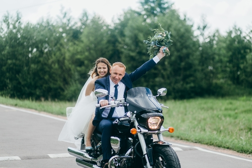 wedding couple getting eloped and riding on a motorbike