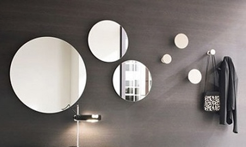multiple rounded mirrors over grey wall