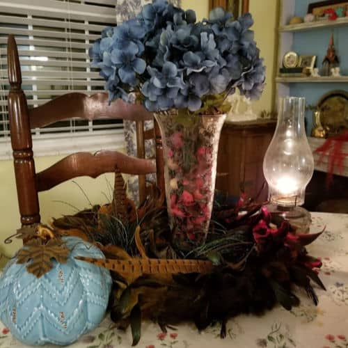 Blue Hydrangea centerpiece surrounded by a feather wreath and a blue pumpkin with an oil lamp