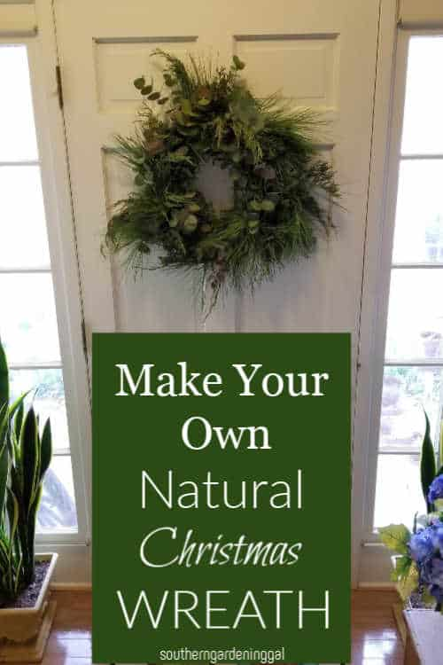 hand made evergreen wreath hanging on white door