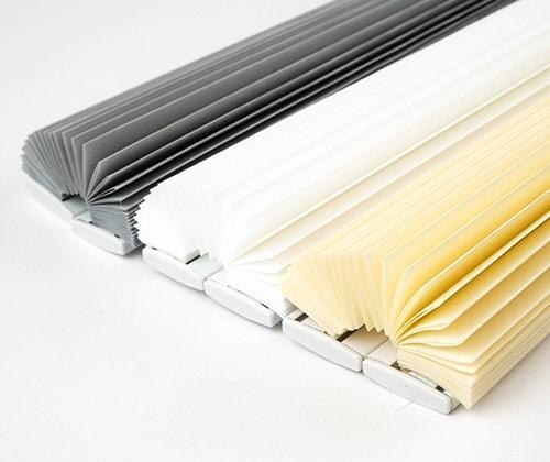 Alledrie de soorten plissè gordijnen: grijs, wit en crème