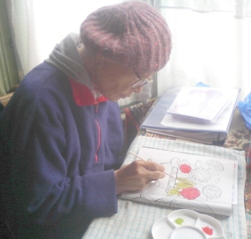 Elly usig watercolours at the community centre