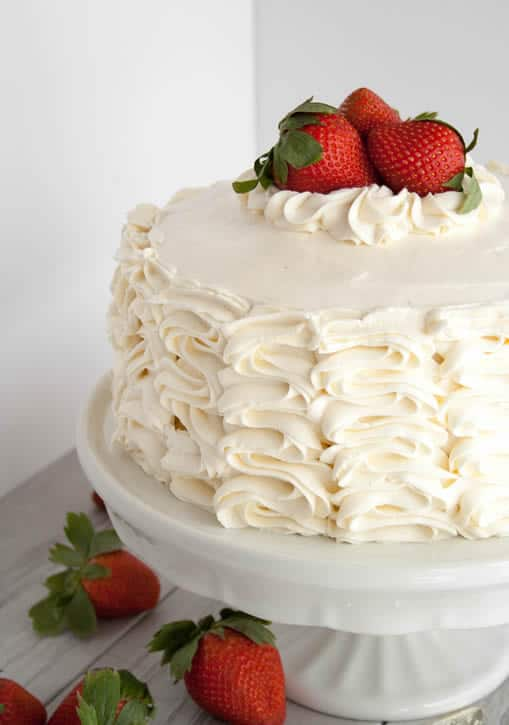 Whipped Cream Cream Cheese Frosting piped on a cake topped with strawberries from themerchantbaker.com