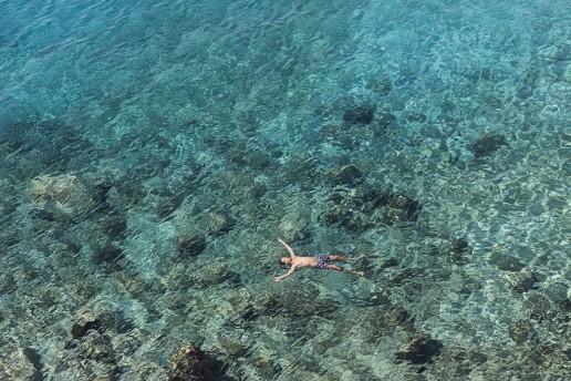Man floating in turquiose sea in Greece