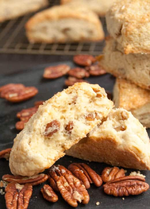 A Brown Sugar Butter Pecan Scone broken in half to display the inside texture and baked in pecans from themerchantbaker.com