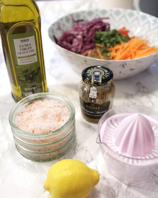 The ingredients for making a lemon mustard and olive oil dressing for vegan salad