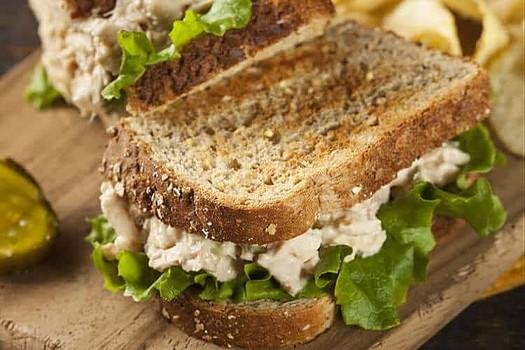 tuna salad sandwich on wood cutting board