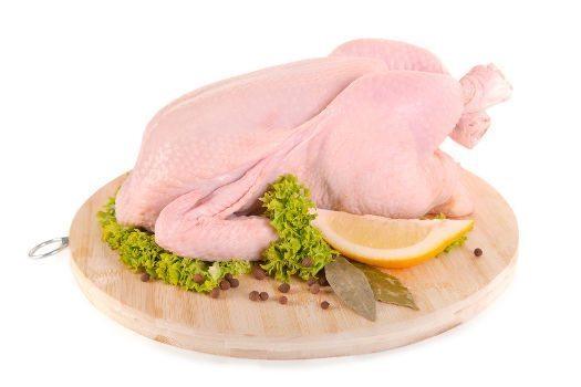 A fresh chicken on chopping board on white bg