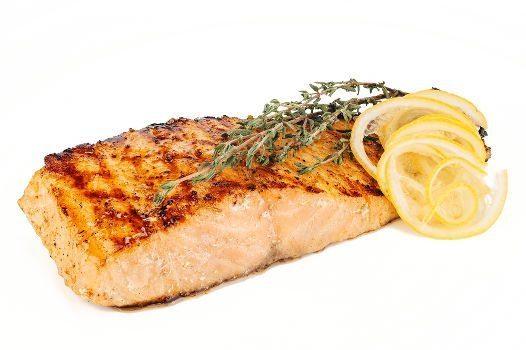 Grilled fish with lemon slices on white bg