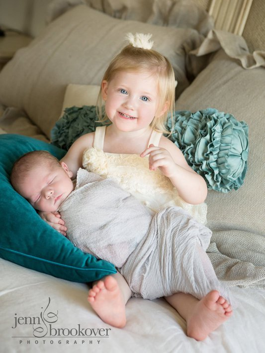 excited big sister smiling and holding her new baby brother at home during newborn session