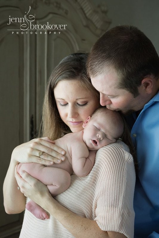 mom and dad snuggling new baby boy in window light at home in San Antonio