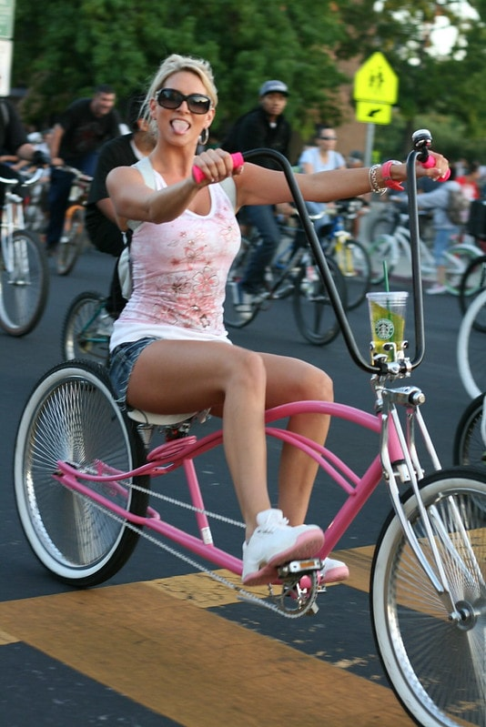 Attractive woman sticking her tongue out at the camera while riding a stretch cruiser bike
