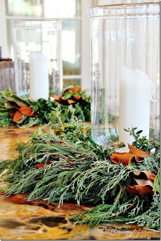 Lush green fern wreaths with fall flowers surround hurricane vases with white candles