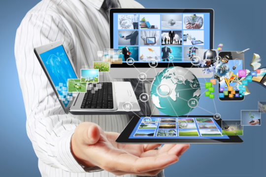 business man holding technology graphics including laptop, smartphone, tablet