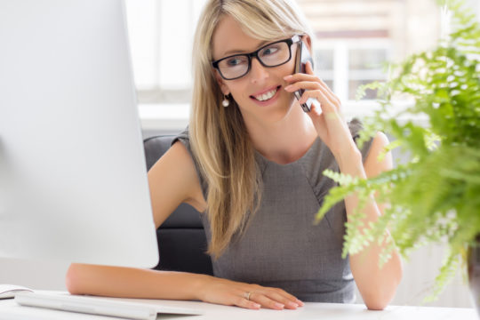 Business woman on phone looking at computer screen