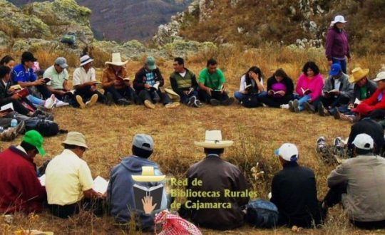 A circle of Peruvians reading together, outside