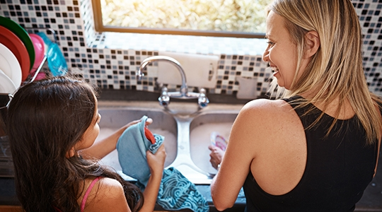 Rearview shot of a cheerful young mother washing dishes with her daughter in the kitchen at home