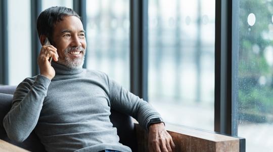 Smiling happy mature asian man with white stylish short beard using smartphone