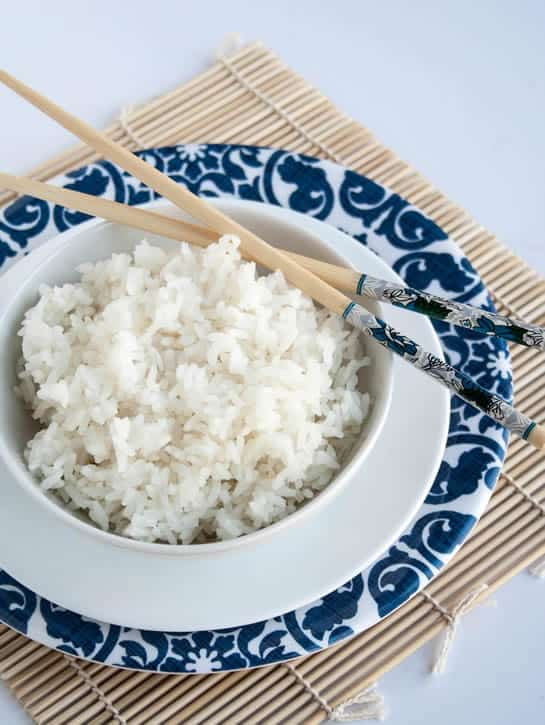 A closeup image of a bowl of Perfect White Rice with chopsticks from themerchantbaker.com