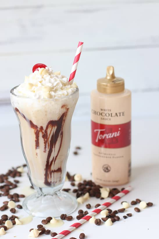 Skip the coffee house and make your own delicious White Chocolate Mocha Frappé at home. This frosty coffee drink recipe is the perfect summer cool down. #Ad #toraniwhitechocolatesauce #coffeedrink #frappe