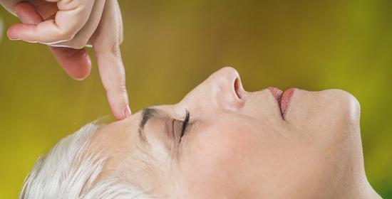 Ayurveda Marma Facial Therapy.  Marma therapy practitioner healing patient Sthapani marma, located between eyebrows. Beautiful senior woman lying with her eyes closed enjoying treatment. Acupressure third eye chakra.