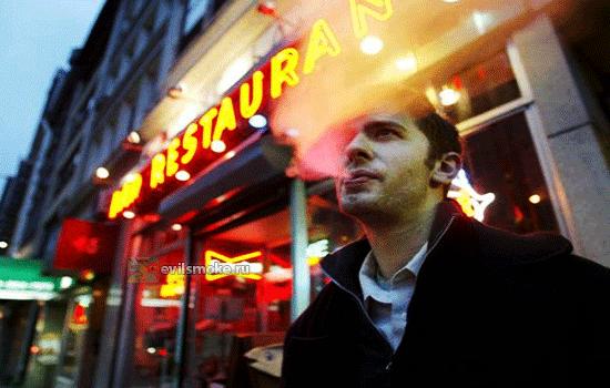 Фото-Парень курит рядом с кафе