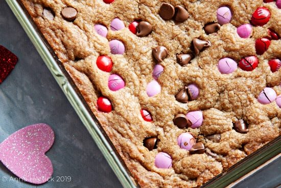 Valentine's day chocolate chip M&M cookie bars in baking pan on gray concrete