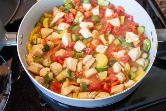 chicken, zucchini, okra, tomatoes and yellow squash in skillet