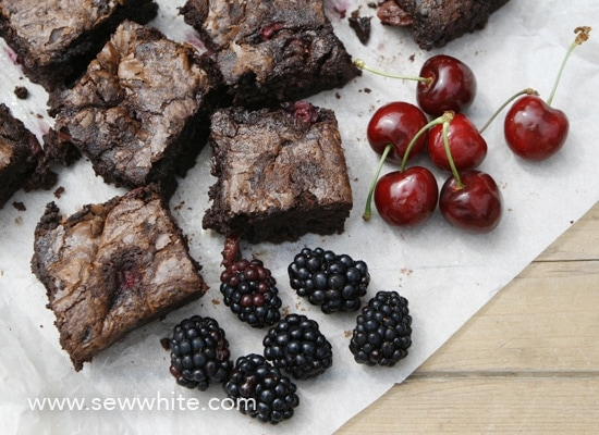 black forest brownies on greaseproof paper with fresh cherries and blackberries.